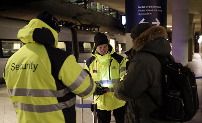 Сотрудники службы безопасности вокзала проверяют документы, чтобы предотвратить нелегальную миграцию в Швецию