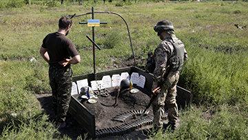 Украинские военные возле импровизированного мемориала их товарищам, погибшим здесь же, рядом с Авдеевкой, Донецкая область