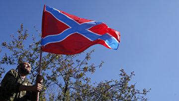 Ополченец устанавливает флаг Новороссии в Донецке
