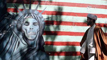 Мужчина на фоне граффити на стенах бывшего посольства США в Тегеране, Иран