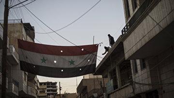 """Бойцы """"Соторо"""" вывешивают флаг Сирии на одной из улиц в городе Камышли провинции Эль-Хасаке на северо-востоке Сирии"""