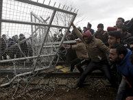 Беженцы и мигранты пытаются сломать часть забора во время протестов на границе Греции и Македонии