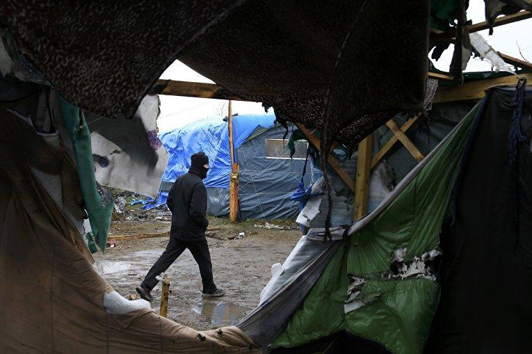 """Житель лагеря эмигрантов """"Джунгли"""", недалеко от Кале идет мимо разрушенных палаток"""