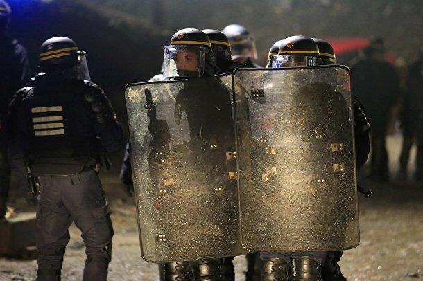"""Сотрудники полиции в лагере мигрантов """"Джунгли"""" возле Кале, Франция"""