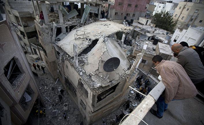 Палестинцы смотрят на дом, разрушенный израильской армией, на окраине города Рамалла