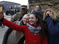 Девушки фотографируются с американскими солдатами во время учений Dragoon Ride, город Салочай, Литва