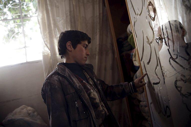 Мальчик рисует пальцем на пыльном зеркале в разрушенном доме