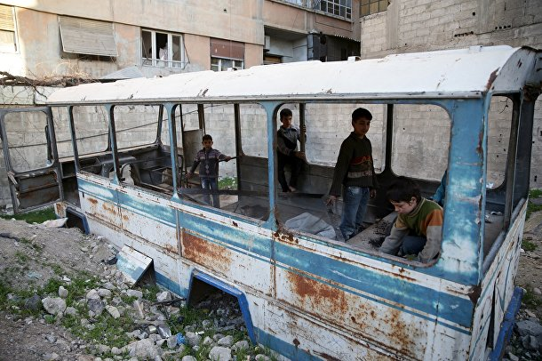 Дети играют в разбитом школьном автобусе в пригороде Дамаска