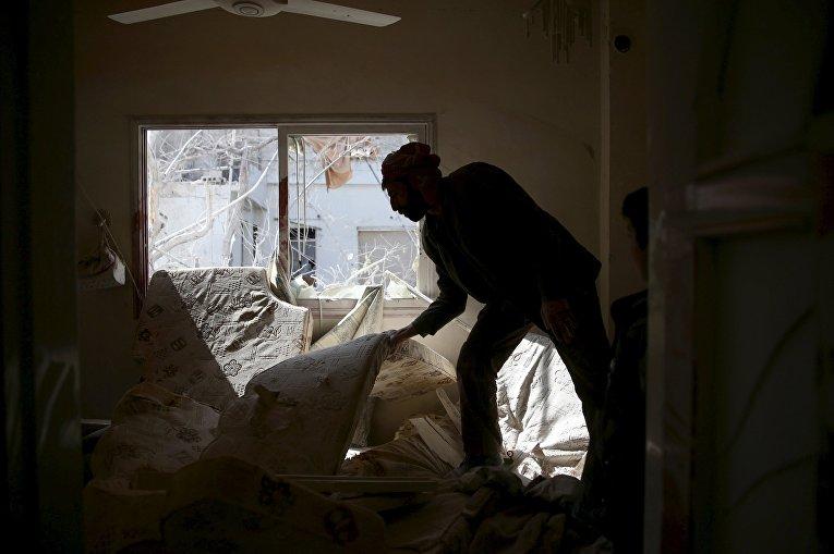 Мужчина ищет свои вещи в одном из домов в пригороде Дамаска