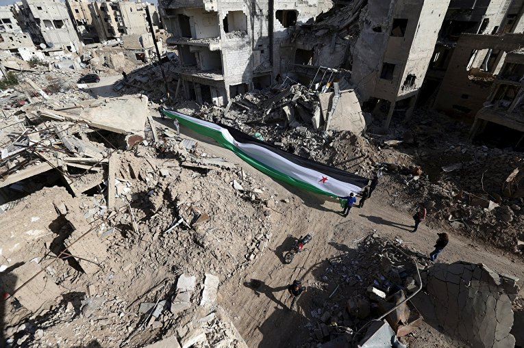 Активисты растянули флаг Свободной сирийской армии во время акции протеста против сил лояльных президенту Сирии Башару Асаду