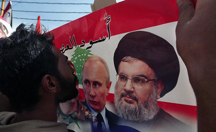 Живущий в Ливане сириец целует плакат с изображением Владимира Путина и Хасана Насраллы во время митинга в Бейруте