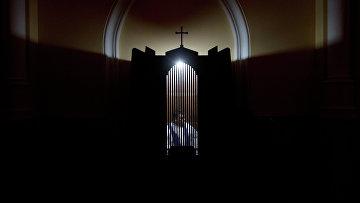 Священник в кабинке для исповеди
