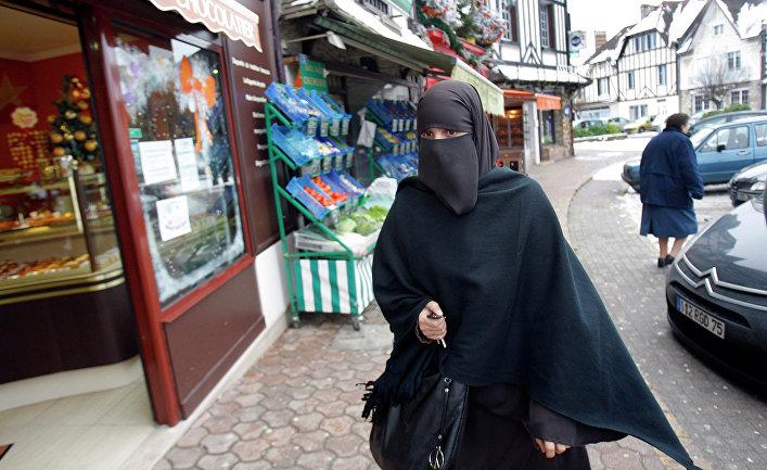 Девушка в мусульманской одежде на улице Ле Мениль-Сен-Дени, Франция