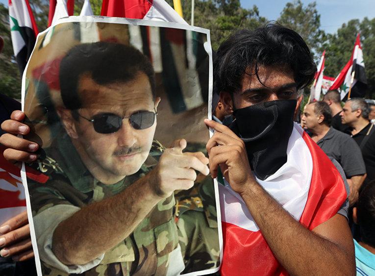 Сириец с плакатом с изображением Башара Асада на митинге в Бейруте