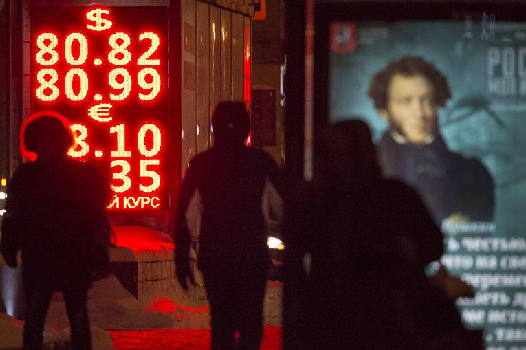 Прохожие идут мимо табло с информацией о курсах обмена валют в Москве