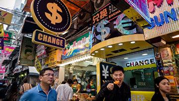 Прохожие гуляют мимо обменных пунктов в Гонконге