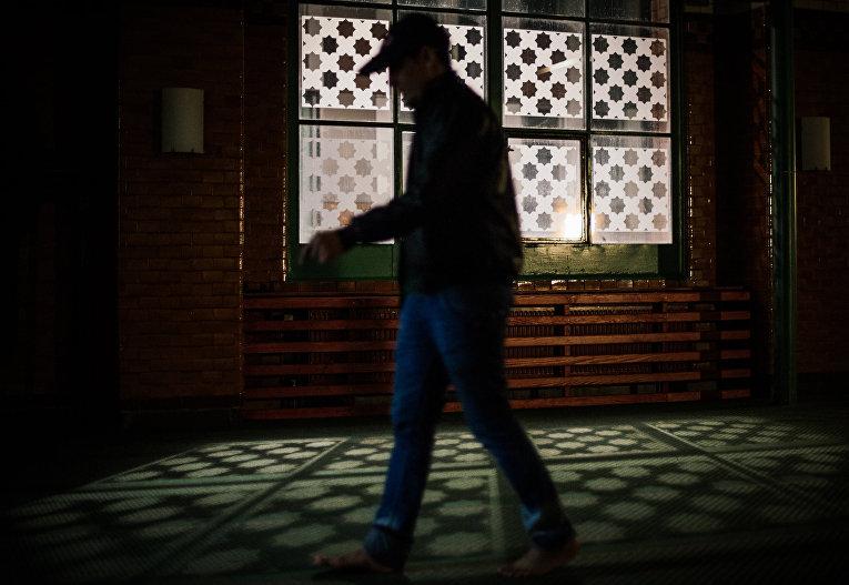 Беженец в молельном зале в центральной мечети в Стокгольме