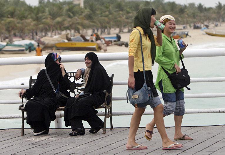 Туристки из Китая гуляют по набережной на Острове Киш в Иране