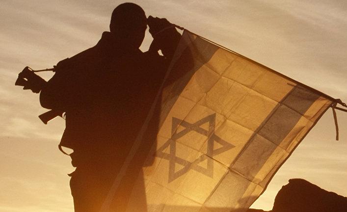 Солдат армии Израиля вешает государственный флаг на танк на израильской стороне границы