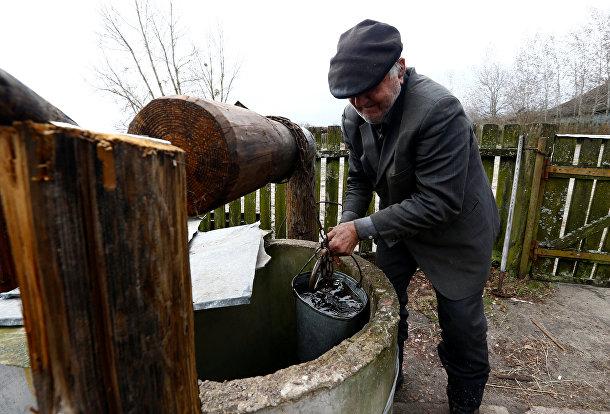 Житель зоны отчуждения Чернобыльской АЭС набирает воду из колодца