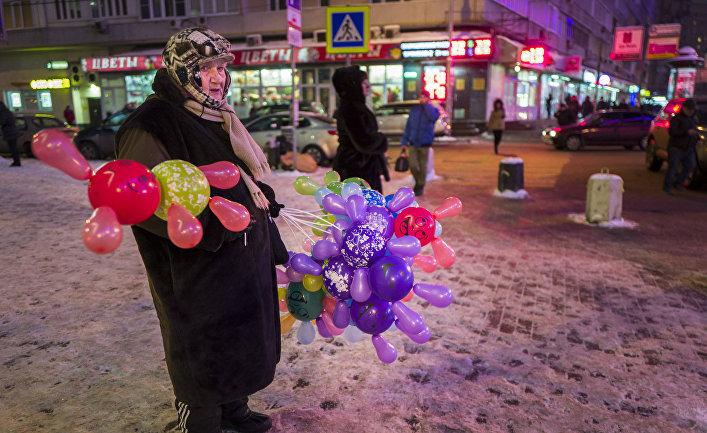 Пожилая женщина продает цветные шары в центре Москвы