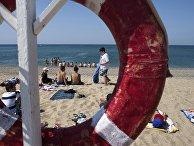 Отдыхающие на пляже Черного моря у детского оздоровительного лагеря «Голубая волна»