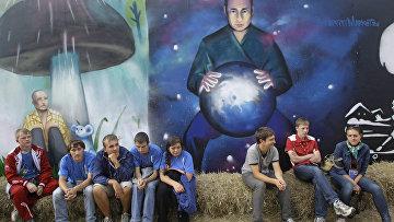 Про-кремлевские активисты рядом с граффити Владимира Путина