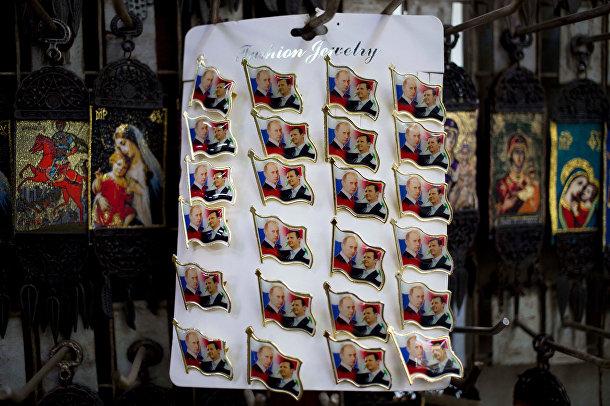 Значки с изображениями президента России Владимира Путина и президента Сирии Башара Асада