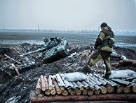 Ополченец стоит у танка украинской армии в Донецкой области