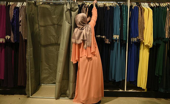 Женщина выбирает платье на 33-ей ежегодной встрече французских мусульман