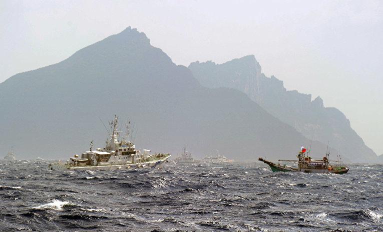 Тайваньская рыбацкая лодка и корабль береговой охраны Японии в районе островов Сенкаку в Восточно-Китайском море
