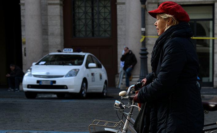 Женщина пользуется велосипедом во время акции протеста таксистов в центре Рима