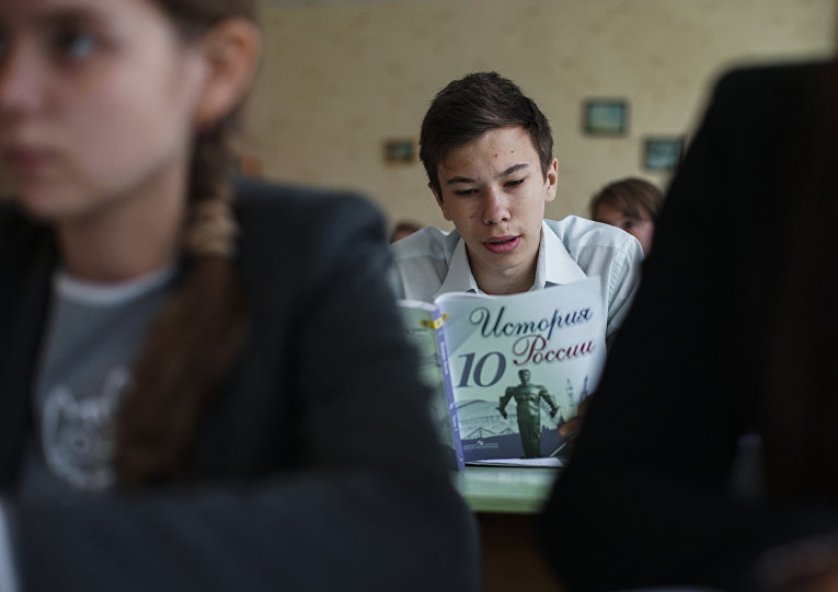 Ученик читает учебник по истории России в одной из школ Донецка