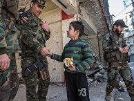 Мальчик общается с военнослужащими Сирийской Арабской армии в жилом квартале города Алеппо