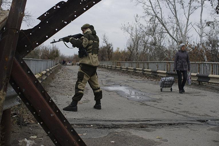 Ополченец на отремонтированном мосту, соединяющем подконтрольные государству и повстанцам территории