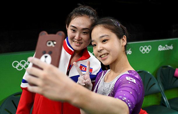 Спортсменка из Южной Кореи Ли Ын Джу делает селфи с Хун Чон, спортсменкой из КНДР