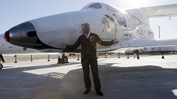 Британский бизнесмен Ричард Брэнсон позирует с частным пилотируемым суборбитальным космическим кораблем многоразового использования SpaceShipTwo