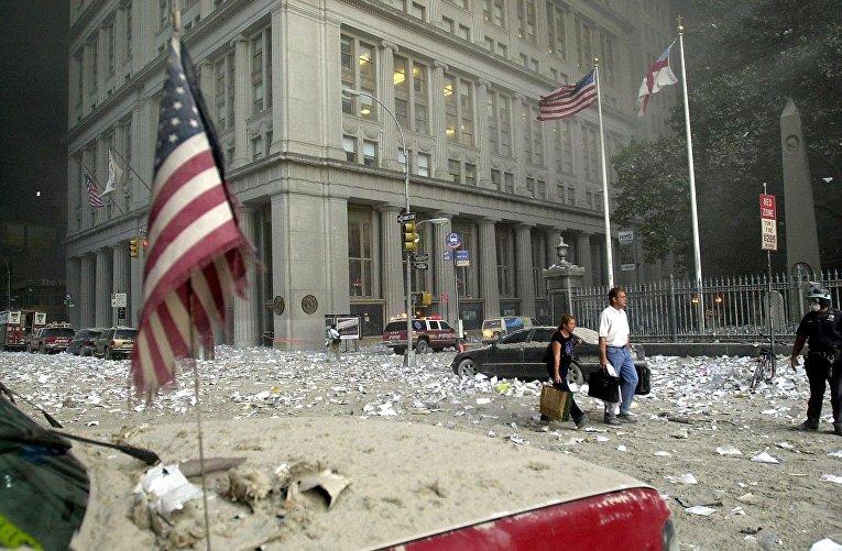 Люди идут среди обломков после разрушения башни Всемирного торгового центра 11 сентября 2001 года в Нью-Йорке