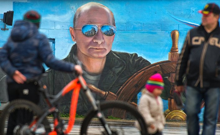 Прохожие у портрета президента России Владимира Путина на стене здания в Ялте