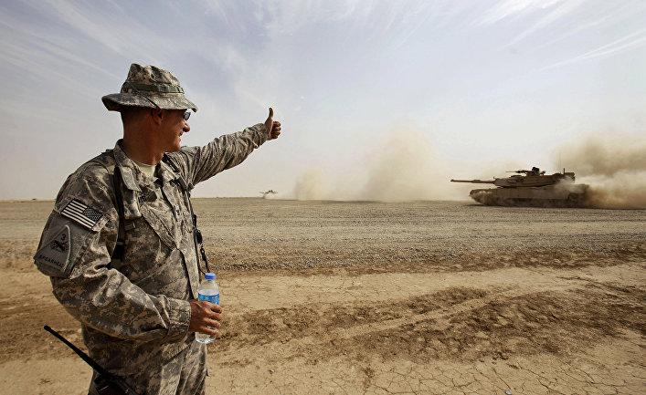 Солдат армии США дает знак экипажу танка М1А1 Abrams во время учений в Ираке