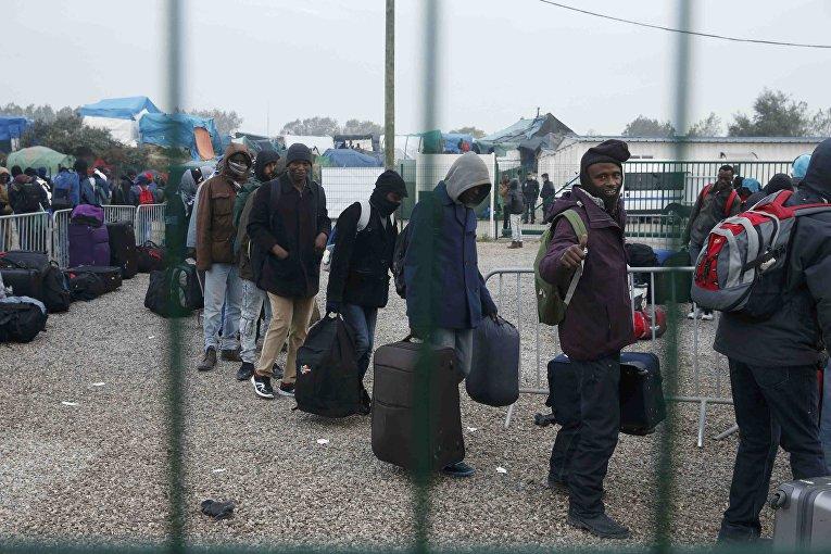 Мигранты ожидают эвакуации во время сноса лагеря «Джунгли»