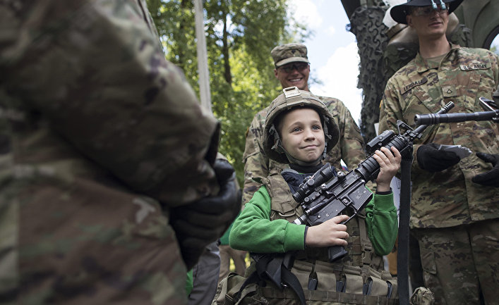 Мальчик с солдатами 2-го кавалерийского полка армии США во время военных учений Dragoon Ride II в Литве