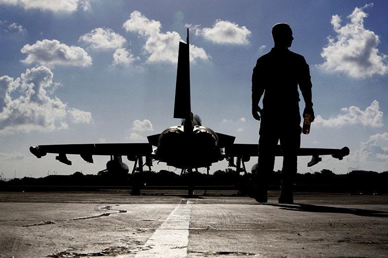 Британский военный возле истребителя «Тайфун» перед взлетом