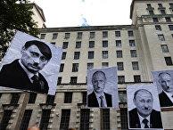 Плакаты, изображающие Владимира Путина в образе Адольфа Гитлера, во время акции протеста в Лондоне