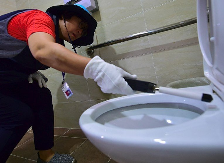 Сотрудница спецотряда полиции в Сеуле проверяет туалет на наличие скрытых камер