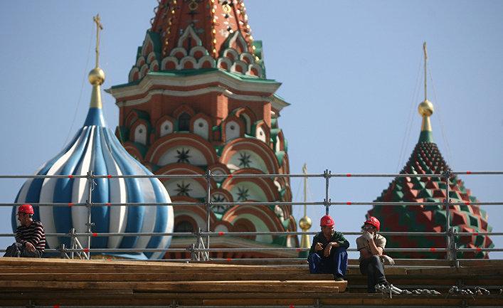 Рабочие отдыхают на строительных лесах на фоне Покровского собора на Красной площади.