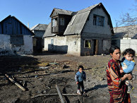Женщина с детьми у своего дома, пострадавшего в результате артиллерийского обстрела
