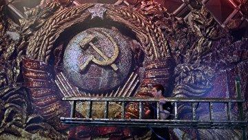 Рабочий с лестницей на фоне изображения герба СССР