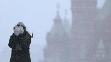 Девушка закрывает лицо от снега во время метели. Архивное фото