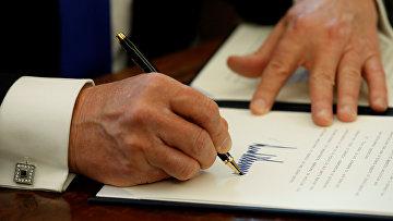 Президент США Дональд Трамп во время подписания документов. 24 января 2017 года